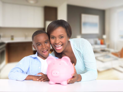 Mother and son saving money for his education in a piggybank and looking happy - isolated over white